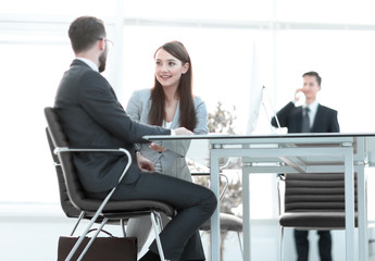 business colleagues talking, sitting behind a Desk
