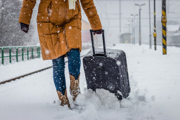 Woman pulling heavy luggage at a snow railroad station