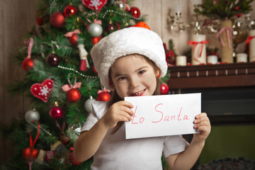 Smiling little girl with letter to Santa near christmas tree
