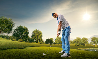 Male golf player on professional golf course. Golfer with golf club taking a shot