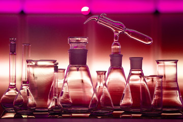 Empty chemical glassware on color background. Group of laboratory empty flasks   on color scientific background reflection on a table