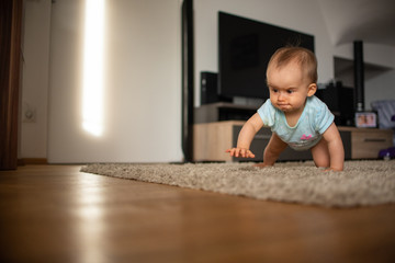 Funny baby goes down on all fours in home