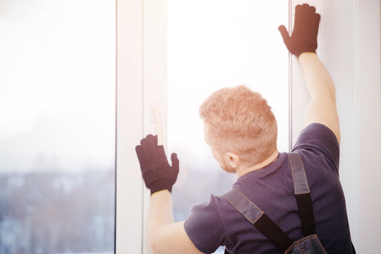 Male builder installs and checks plastic windows in apartment house
