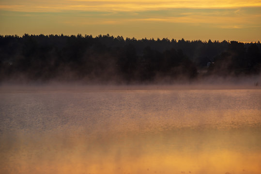colorful misty sunset on the river in summer