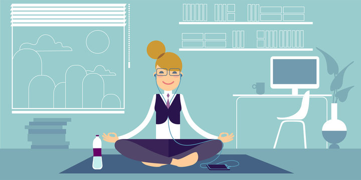 An Bespectacled yoga girl in headphones meditates in the office, sitting on a pilates mat in an easy sukhasana pose. Beside her a bottle of water and a computer on the table.