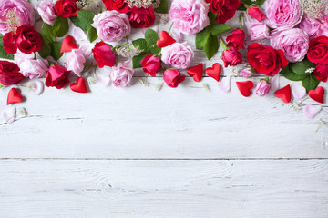 Roses and red hearts on a wooden background