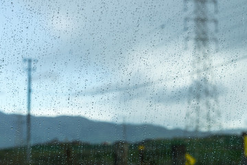 Drops of rain on the window; blurred electricity lines in the background; shallow depth of field