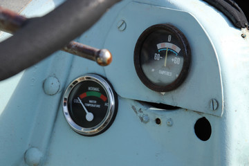 Vintage gauges on the dashboard of an old tractor. Control and measurement concept image.