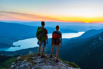 Hikers enjoying scenic view of valley with lake at sunset, couple enjoying summer outdoor trek in mountains, active lifestyle, two people backpacking