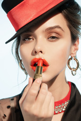 The girl in the hat paints her lips with lipstick