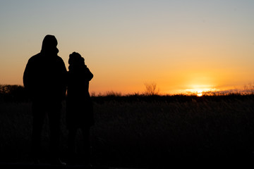 Silhouette of a couple standing and watching the sunset