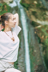 Woman practicing yoga in front of waterfall.
