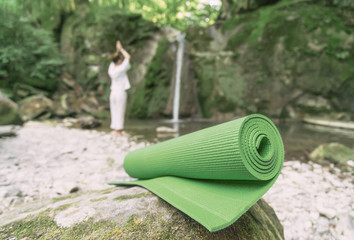 Yoga mat in front of silhouette of woman.