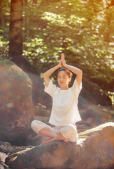 Woman meditating in pose of lotus in forest.