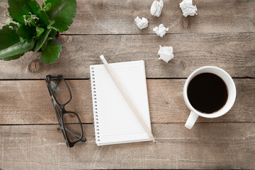 Notebook with drinking coffee on wooden table
