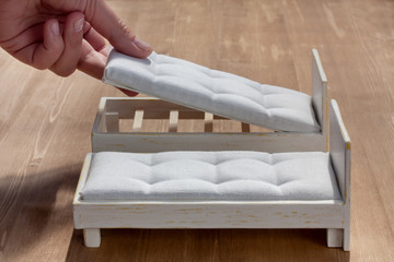 Woman's hand putting down a new mattress on a doll bed, preparing bedding for two small white wooden beds, close up