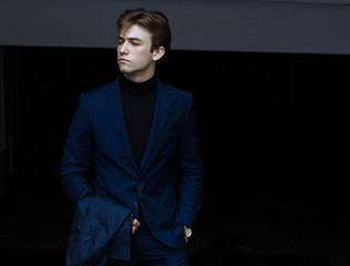 portrait of attractive man in blue suit with coat in hand on black background