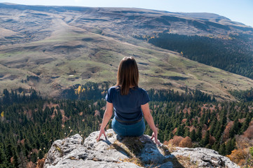 a young active girl sits on the edge of a rock, look at the Caucasus mountains.