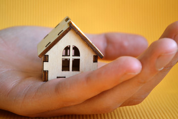 Wooden toy house model in man's hand on yellow background front view