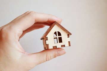 Wooden toy house model in woman's hand on white background front view