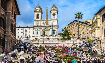 Piazza di Spagna, viewed from the Via Condotti. A lot of people are on the Spanish Steps near church Santissima Trinità dei Monti and Obelisk Sallustiano. Rome.