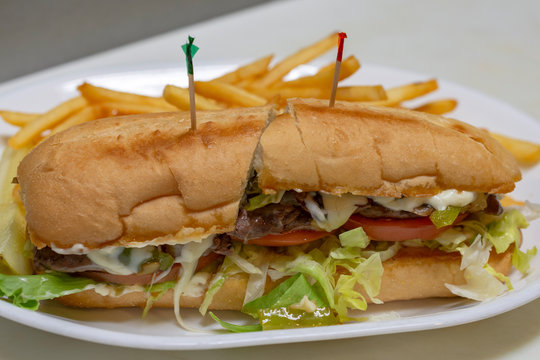 Philadelphia cheesesteak sandwich on a sub bun.  White platter with toothpicks.  Halved.  French fries in background.