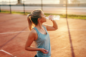 Sporty Caucasian blonde woman standing on the court and drinking water after morning exercises.