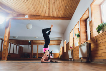 Young yogi attractive woman practicing yoga concept, standing in salamba sirsasana exercise, headstand pose, working out, wearing sportswear, black tank top and pants, full length, loft background.