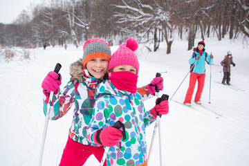 little girls cross-country skiing in the winter forest in the snow
