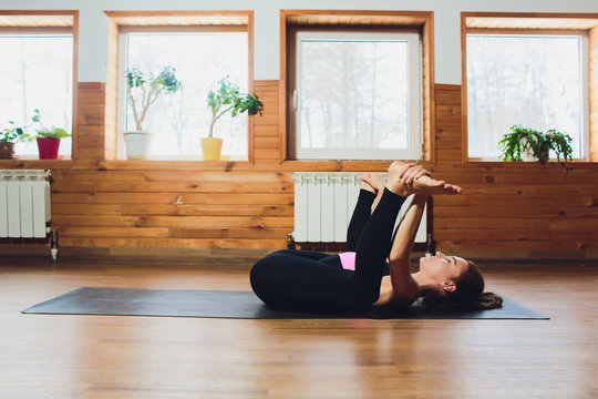woman practicing yoga, stretching in Ananda Balasana exercise, Happy Baby pose, working out, wearing black sportswear, cool urban style, full length, grey studio background, side view.