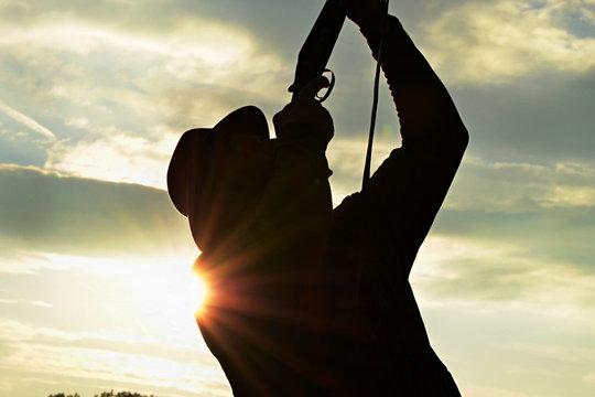 hunter shooting with a shotgun, silhouette against the sundown