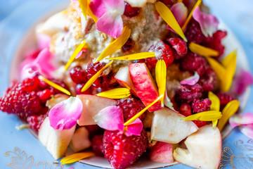 Fototapeta Macro closeup of colorful bowl of ice cream topped with vibrant pink rose flower petals, red raspberries, fruit salad, dessert obraz