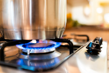 Macro closeup of modern luxury gas stove top with blue fire flame knobs and stainless steel pot...