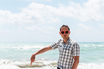 Young man hipster millennial funny humor face on beach during sunny day with red sunglasses in Miami, Florida with ocean in background hands finger pointing down