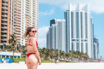 Young woman looking back millennial on beach during sunny day in Miami, Florida with skyscrapers hotels apartments condo urban background, red swimsuit