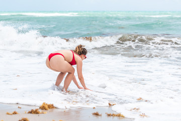 Young woman on beach during sunny day in Miami, Florida bending over reaching sand water wave shore with hands arms and seaweed in ocean