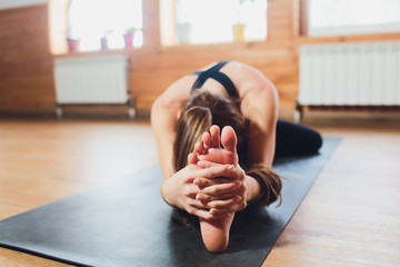 Young sporty attractive woman practicing yoga, doing Revolved Head to Knee Forward exercise, Parivrtta Janu Sirsasana pose, working out, wearing sportswear, black pants, indoor close up, yoga studio.
