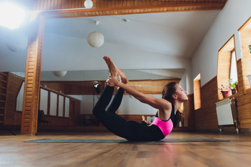 Young sporty woman practicing yoga, doing Double Leg Kicks exercise, Salabhasana pose, working out, wearing sportswear, grey pants and top, indoor close up, yoga studio.