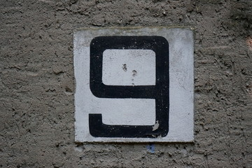 Painted Number 9 Nine on concrete wall on an abandoned summer camp house