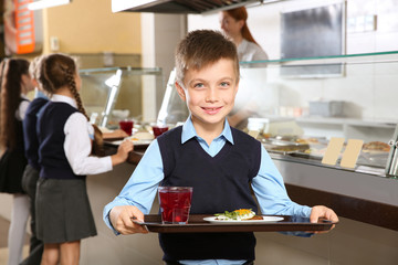 Cute boy holding tray with healthy food in school canteen