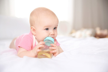 Pretty baby lying with bottle on bed at home. Space for text
