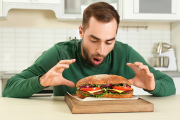 Young hungry man and tasty sandwich in kitchen