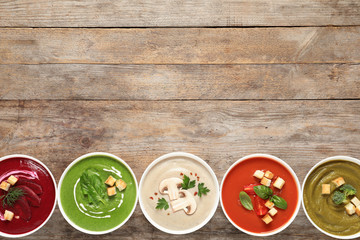 Various cream soups in bowls and space for text on wooden background, top view