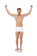 Fit man standing on bathroom scale against white background. Weight loss