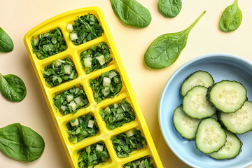 Flat lay composition with ice cube tray, fresh spinach and cucumber on color background