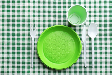 Composition with plastic dishware on checkered tablecloth, top view. Picnic table setting