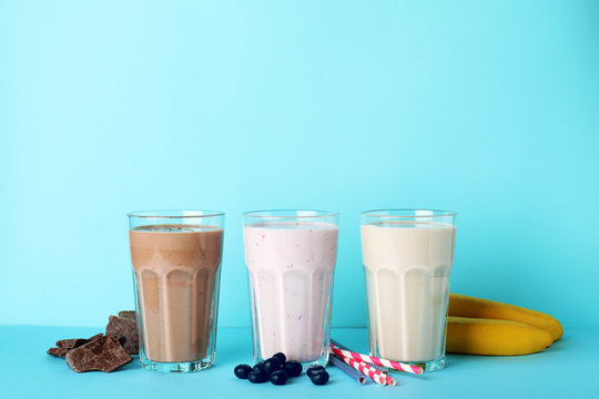 Glasses with different protein shakes and ingredients on color background. Space for text