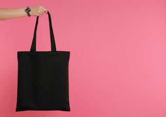 Woman holding eco bag on color background. Mock up for design