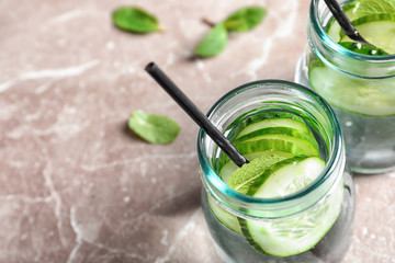 Jars with fresh cucumber water on grey background, closeup. Space for text