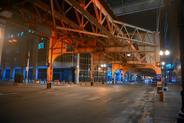 Wall Mural - Deserted downtown city street intersection under a vintage railroad train subway bridge at night in Chicago